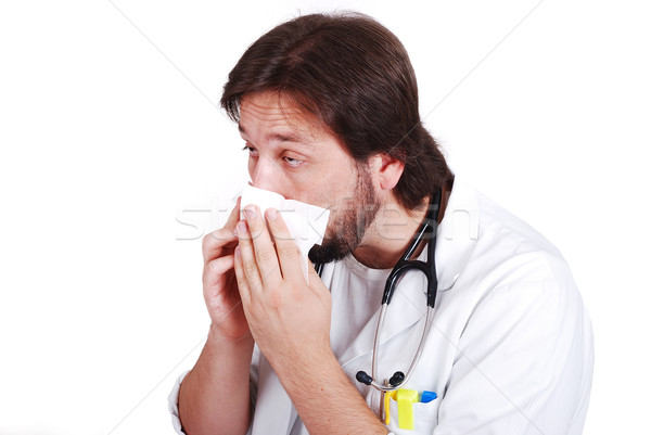 Young male doctor got fly and cleaning his nose with tissue Stock photo © zurijeta