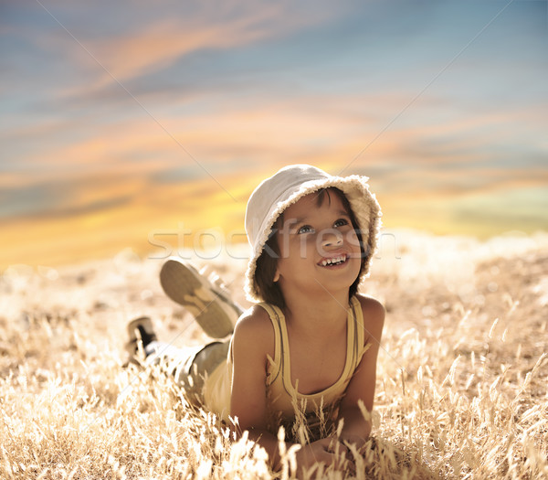 Happy boy laying on ground, yellow grass, summer to fall period Stock photo © zurijeta