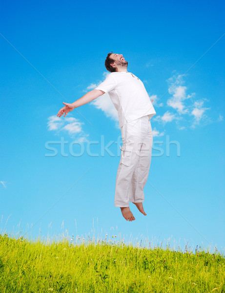 Happy young mane in white jumping on beautiful meadow Stock photo © zurijeta