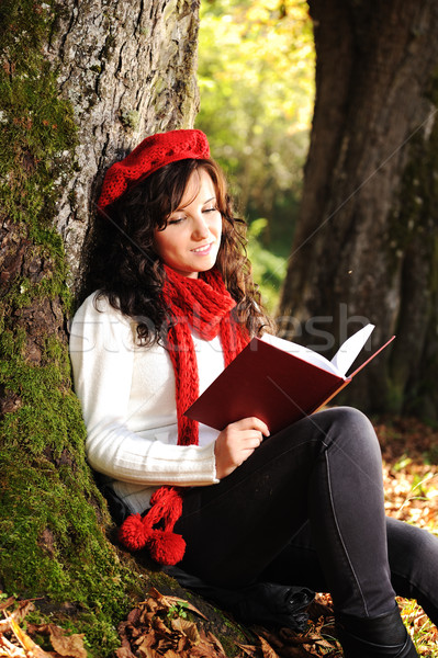 Beauty gorgeous autumn girl sitting in nature beside the tree and reading the book Stock photo © zurijeta