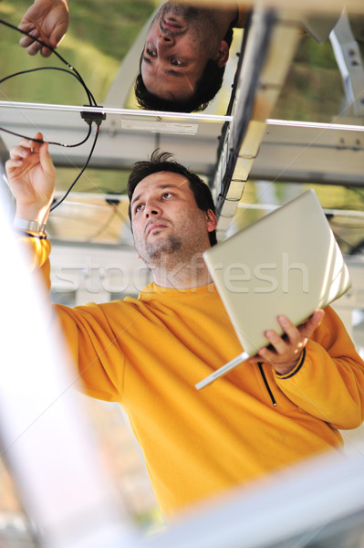 Young expert engineer working using laptop and connecting wires Stock photo © zurijeta