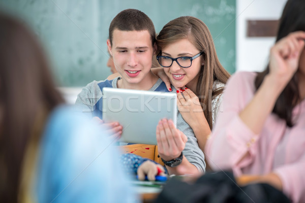 Happy classmates looking at a tablet Stock photo © zurijeta
