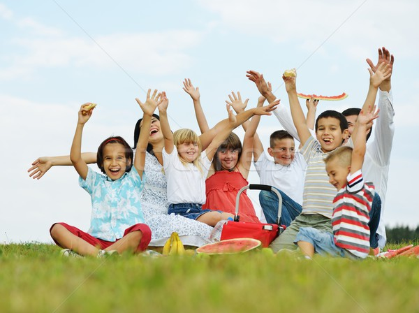 Family with children having picnic time on green meadow in natur Stock photo © zurijeta