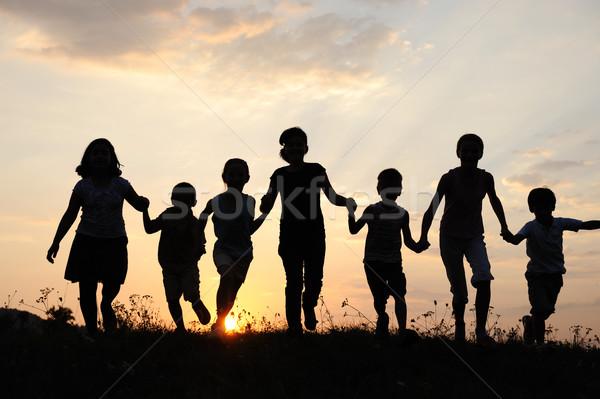 Children running on meadow at sunset time Stock photo © zurijeta
