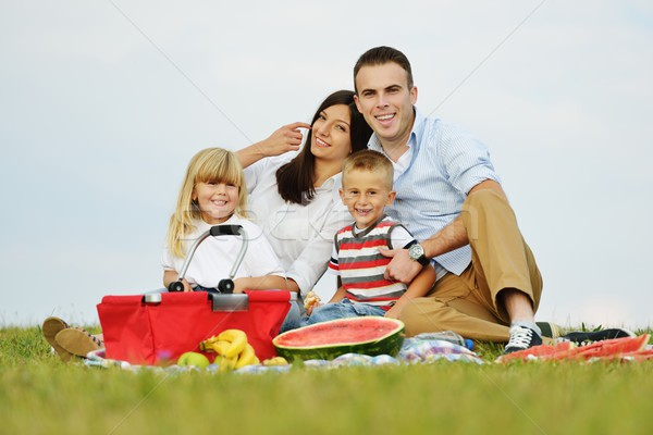 Stock photo: Family with children having picnic time on green meadow in natur