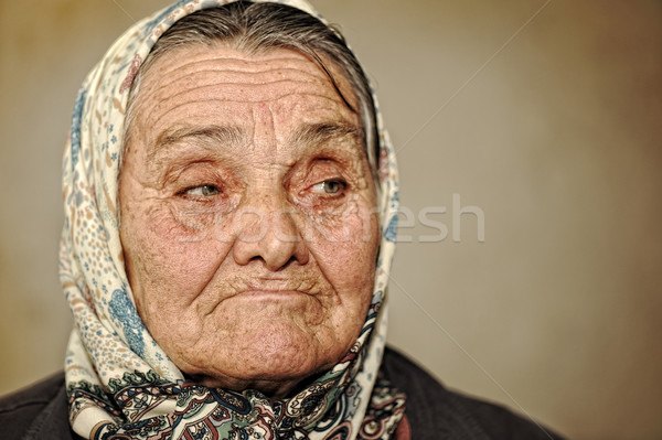 Portrait of mature woman with green eyes and scarf on head looking aside Stock photo © zurijeta
