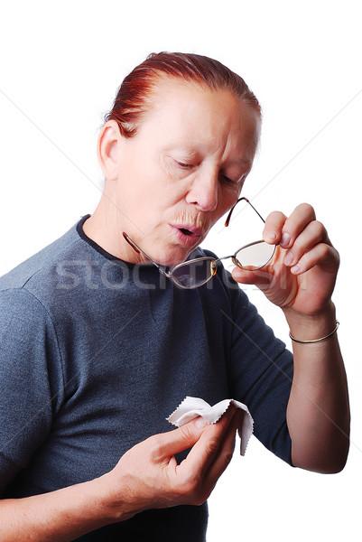Elderly woman cleaning her glasses Stock photo © zurijeta