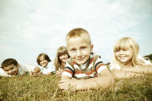 Filtered image of happy children on summer grass meadow in natur Stock photo © zurijeta