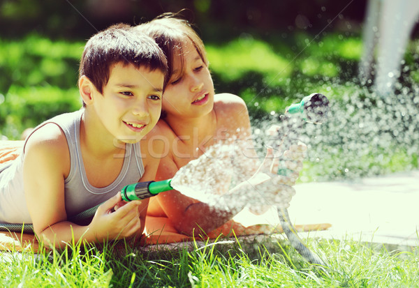 Children playing and splashing with water sprinkler on summer gr Stock photo © zurijeta