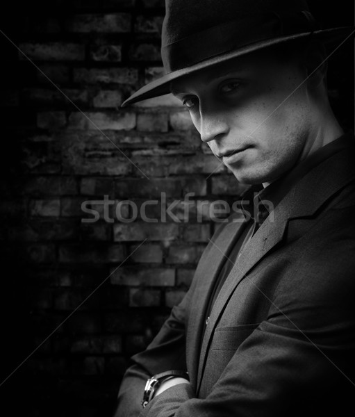 Man with hat standing against dark brickwall background Stock photo © zurijeta