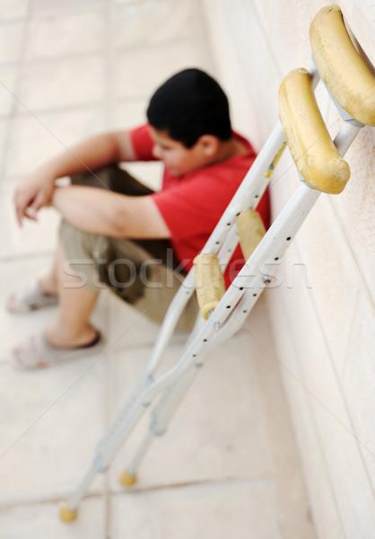 kid sitting  on the street with a crutches  Stock photo © zurijeta