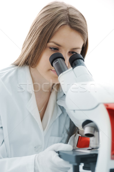 Beautiful female researcher using a microscope in a lab Stock photo © zurijeta