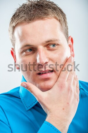Handsome young man scratching his beard Stock photo © zurijeta