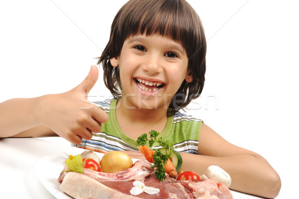 Cute positive boy and raw meat and vegetables in plate reading for cooking Stock photo © zurijeta