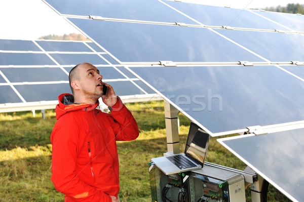 Stock photo: Engineer working with laptop by solar panels, talking on cell ph