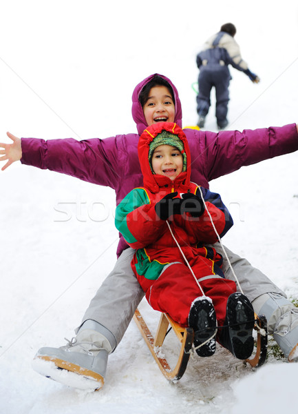 Boy and girl sledging on snow, happiness for brother and sister Stock photo © zurijeta