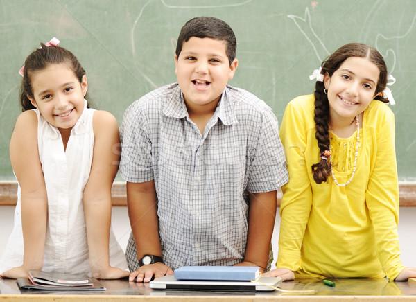 Three happy children standing at board, posing beside the table Stock photo © zurijeta