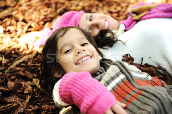 Cute boy lying in the Autumn fall leaves with his mother Stock photo © zurijeta