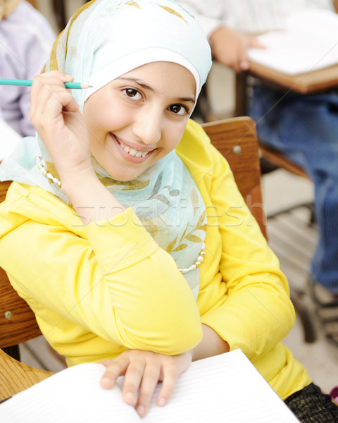 Cute Muslim arabic girl sitting on the chair and holding pencil - at school Stock photo © zurijeta