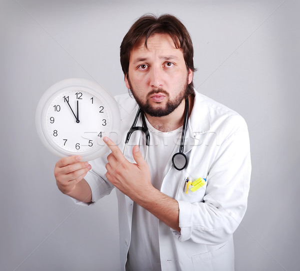 male doctor holding out an alarm clock ticking ever closer to 12  Stock photo © zurijeta