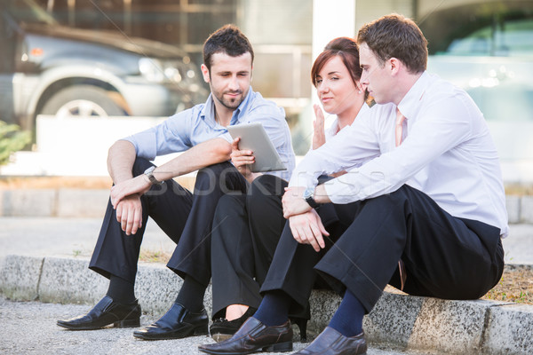 Three people with tablet on sidewalk Stock photo © zurijeta