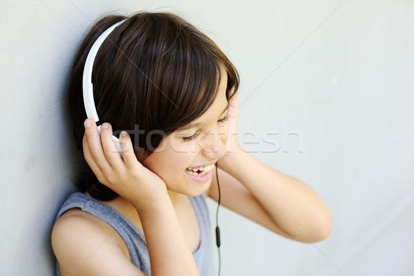 Child listening to music on headphones and enjoying Stock photo © zurijeta