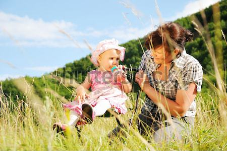 Baby girl siting in nature and drinking milk from bottle Stock photo © zurijeta