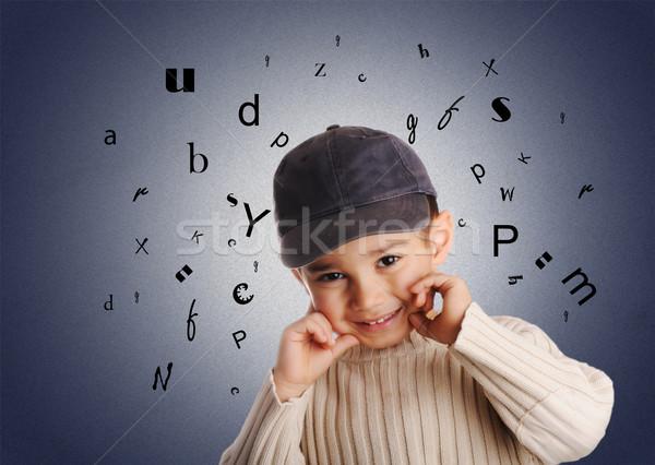boy with denim cap, letters of alphabet on background Stock photo © zurijeta