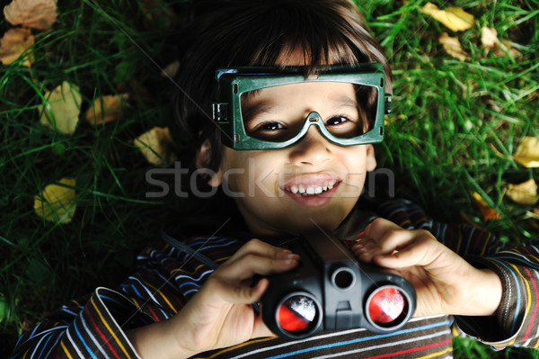 Cute positive boy with glasses and binoculars laying on ground and smiling Stock photo © zurijeta