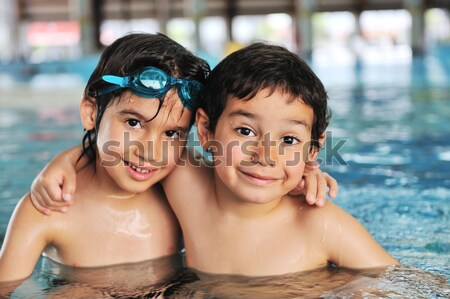 Happy young children, boy and girl, relaxing on the side of a swimming pool wearing blue and pink go Stock photo © zurijeta