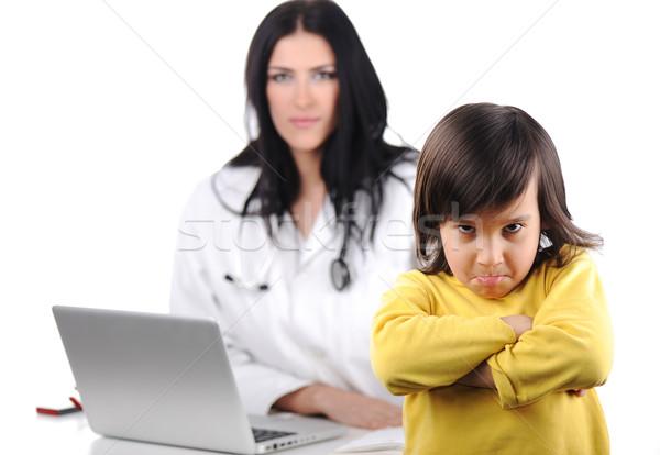 Young female doctor examining little cute angry child refusing examining Stock photo © zurijeta