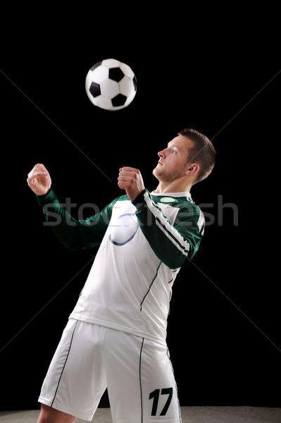 Footballer on black background Stock photo © zurijeta