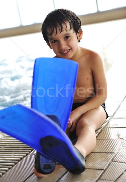 Kid on pool with flippers on feet Stock photo © zurijeta