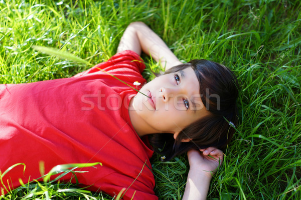 Little boy enjoying summer time lying on meadow green grass with Stock photo © zurijeta