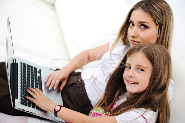 Mother and daugther with laptop on sofa Stock photo © zurijeta
