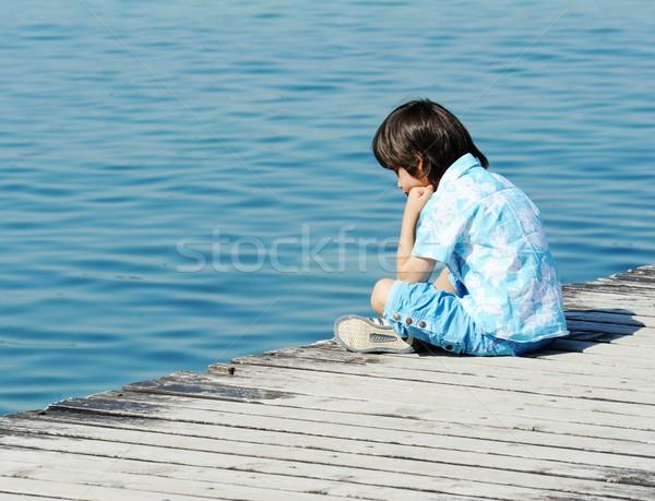 Child by wooden dock on a beautiful sea Stock photo © zurijeta