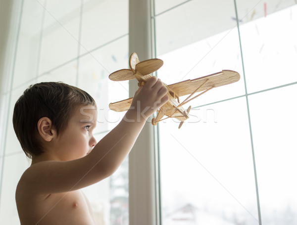 Happy little kid wants to fly with his airplane trough the windo Stock photo © zurijeta