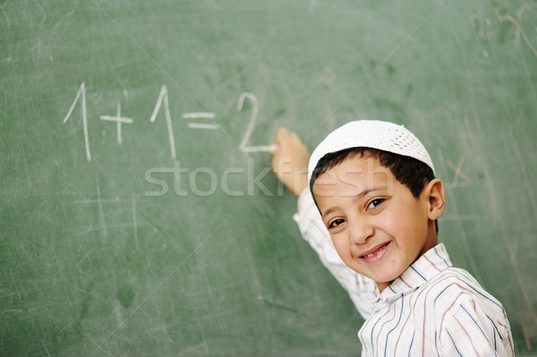 Very cute and positive kid smiling and writing on school board Stock photo © zurijeta