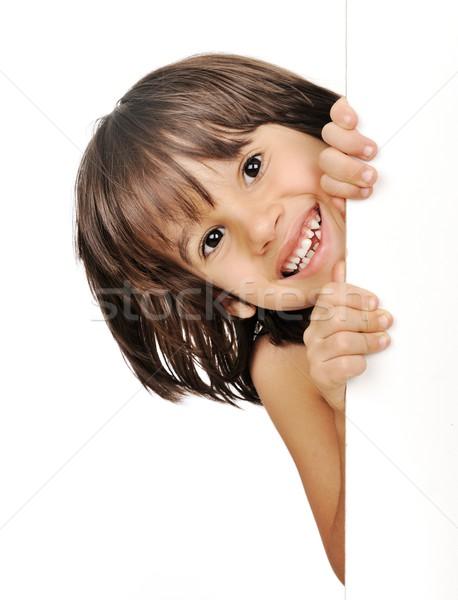 Stock photo: Little boy peeking from behind the advert