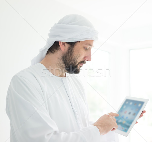 Arabic man wearing traditional clothes using tablet Stock photo © zurijeta