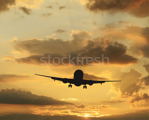 Stock photo: Rare colorful sky at sunset and airplane taking off