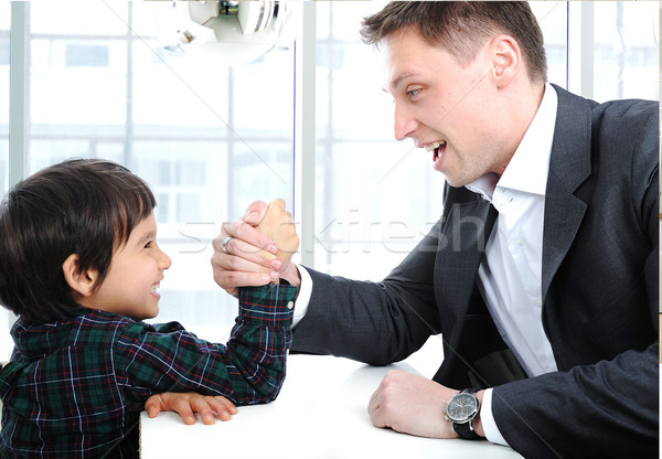 Young father and son wrestling with arms, competition fight parenting concept indoor Stock photo © zurijeta