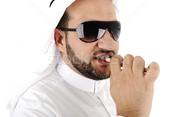 Arabic adult cleaning teeth with miswak Stock photo © zurijeta