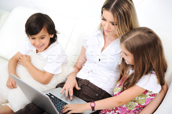 Mother with daugther and son using  laptop on sofa indoor Stock photo © zurijeta