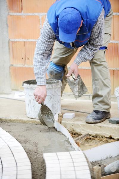 Mason worker making sidewalk pavement with stone blocks Stock photo © zurijeta