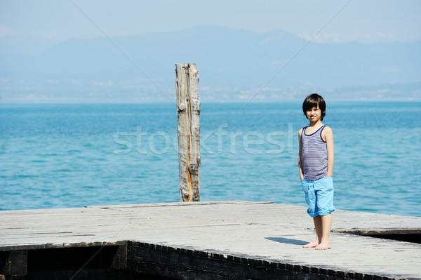 Little boy walking on dock by beautiful sea Stock photo © zurijeta