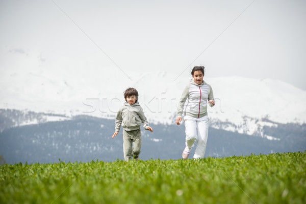Boy and girl running and jumping on spring field in Alps Stock photo © zurijeta