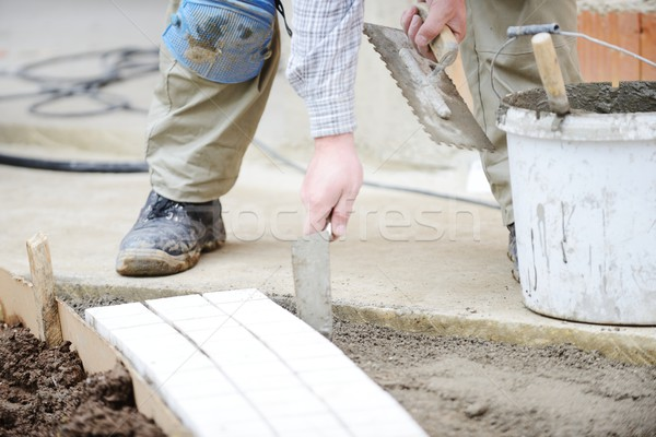 Mason worker making sidewalk pavement with stone blocks Stock photo © zurijeta