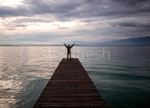 örömteli férfi dokk kezek levegő áll Stock fotó © zurijeta