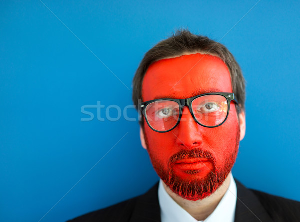 Businessman with colorful red and blue painted face Stock photo © zurijeta
